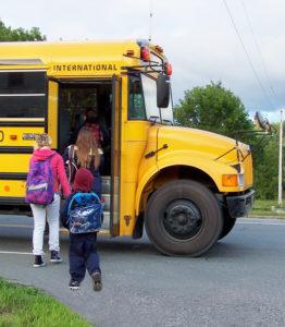 children boarding school bus with backpacks