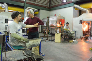Billy Cioffredi, PT, Founder assisting a glassblower at Simon Pearce.